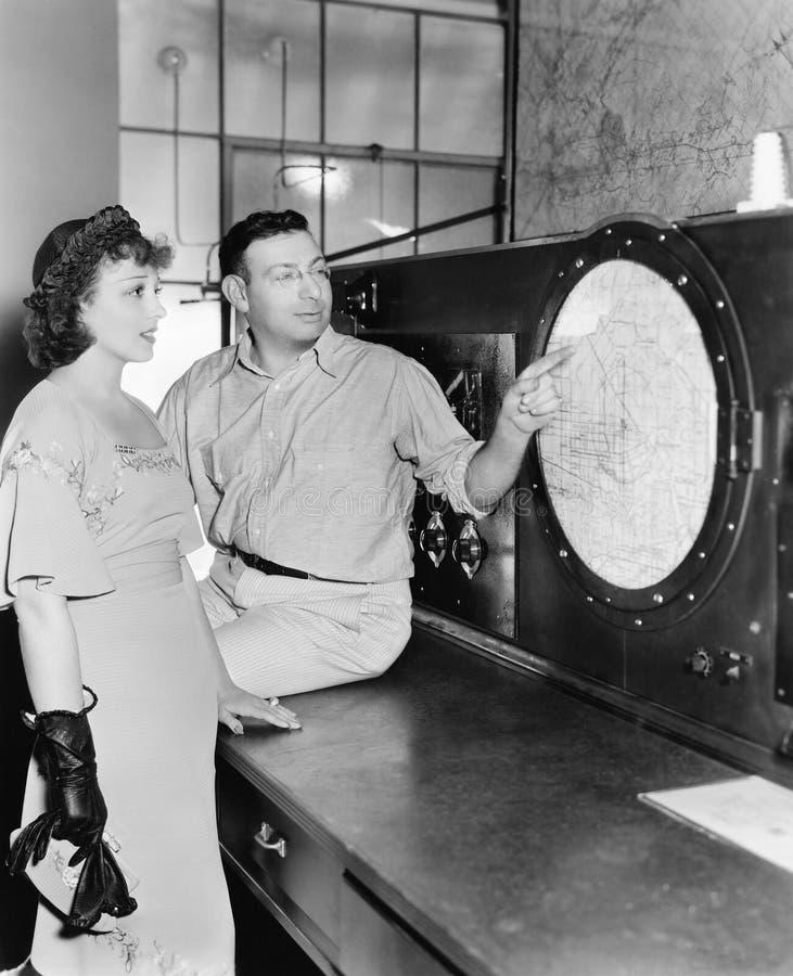 Équipez l'explication au sujet du radar à une jeune femme dans une salle de commande (toutes les personnes représentées ne sont p image stock