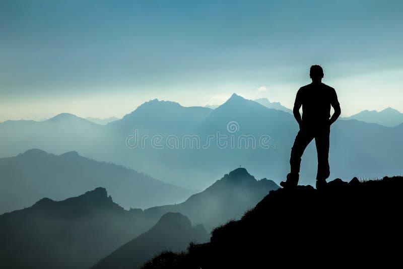 Équipez l'observation dreamfully vers les silhouettes spectaculaires de gamme de montagne image stock