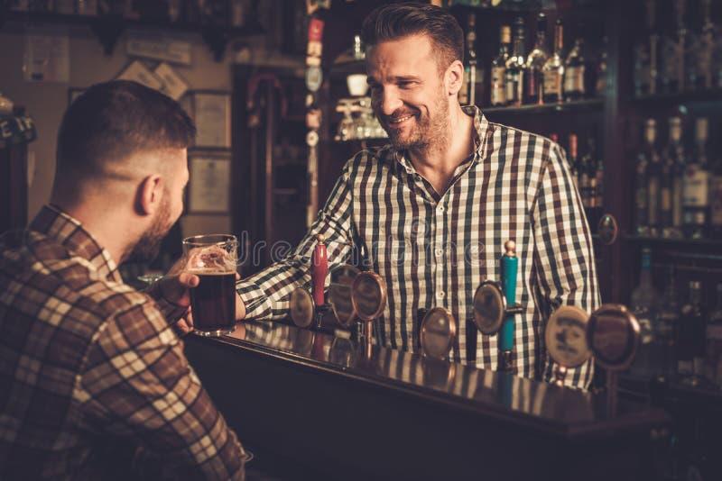 Équipez la causerie avec un barman dans un bar photos libres de droits