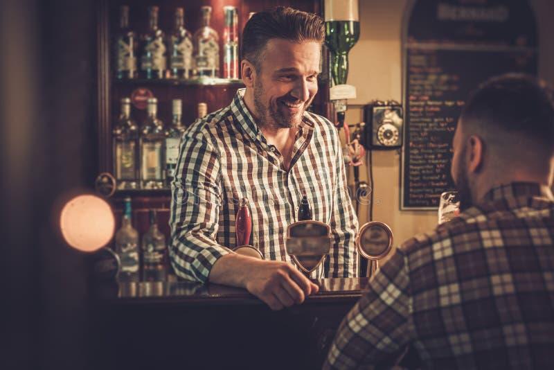 Équipez la causerie avec un barman dans un bar image stock