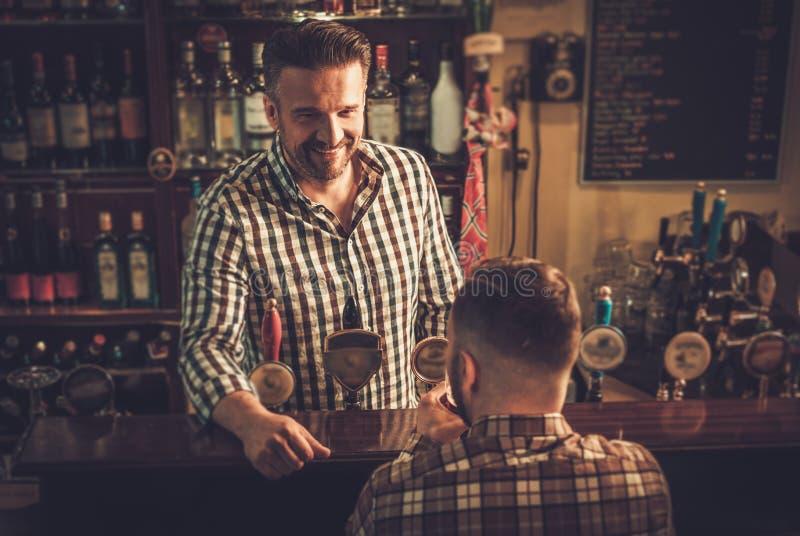 Équipez la causerie avec un barman dans un bar images libres de droits