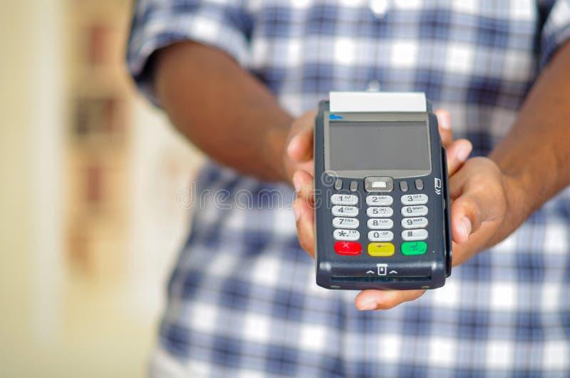 Équipez la chemise bleue de port de modèle de place blanche retardant le terminal de paiement par carte de crédit devant l'appare photos libres de droits