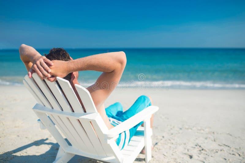 Équipez la détente sur la chaise de plate-forme à la plage photographie stock libre de droits