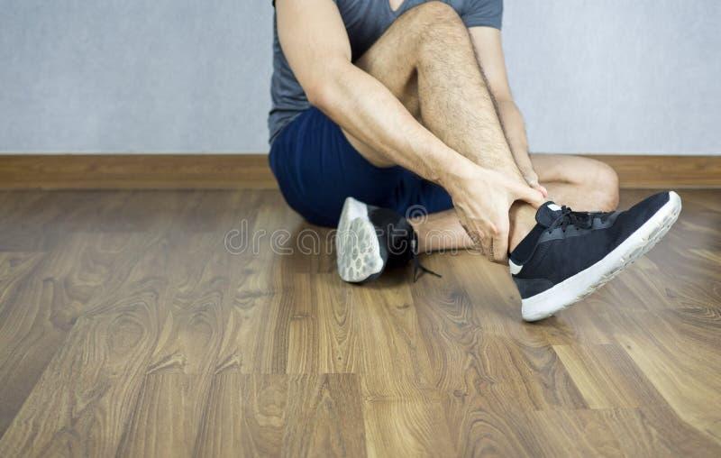 Équipez la douleur de cheville du fonctionnement, pulser, marchant, reposez-vous sur le plancher image stock
