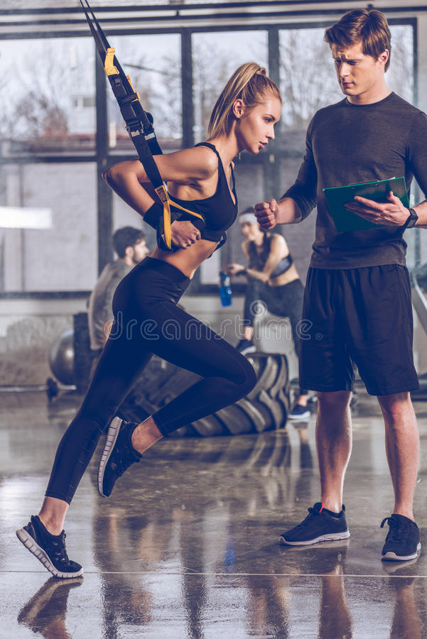 Équipez la femme folâtre de aide s'exerçant avec l'équipement de gymnase de trx image libre de droits