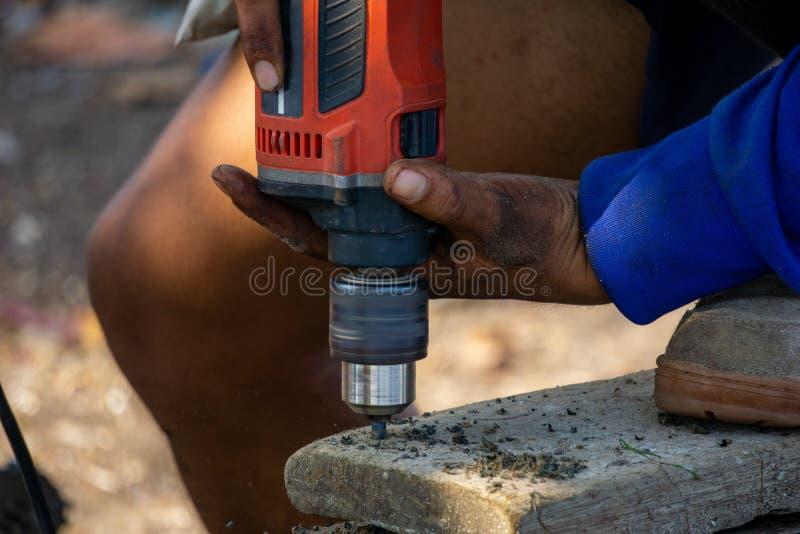 Équipez la foreuse portative électrique d'utilisation pour forer sur une vieille planche en bois image stock
