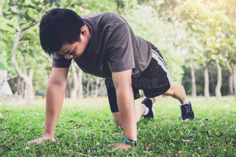 Équipez la forme physique de séance d'entraînement d'exercice de pompe faisant dehors sur l'herbe dedans photos libres de droits