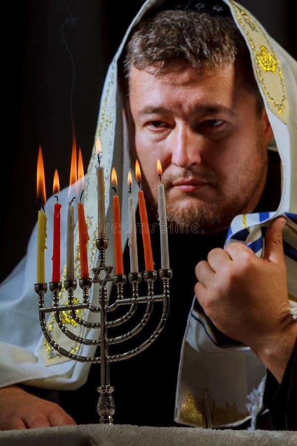 équipez la main allumant des bougies dans la table de menorah servie à Hanoucca
