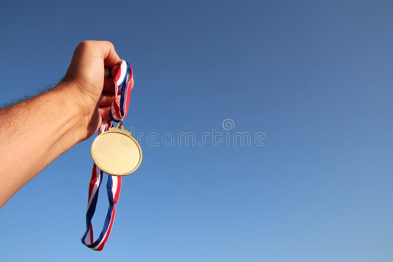 Équipez la main augmentée, en tenant la médaille d'or vide contre le ciel concept de récompense et de victoire Pour la moquerie  photos libres de droits
