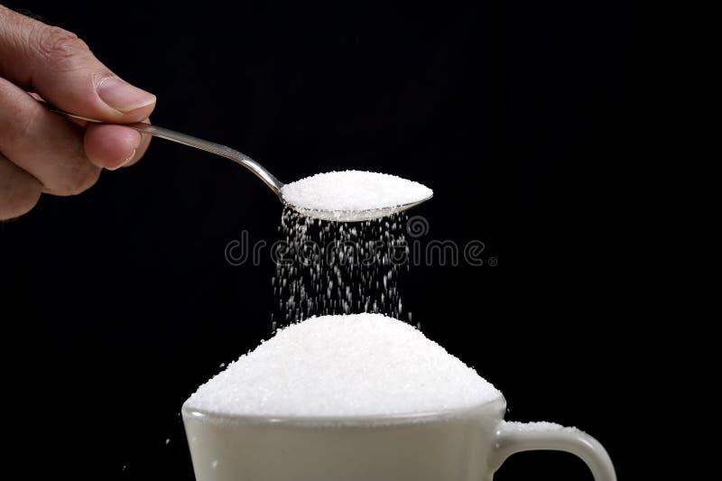 Équipez la main avec la cuillère versant un sort fou dans la pleine tasse de café dans le concept de dépendance image stock