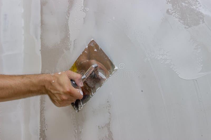 Équipez la main avec la truelle plâtrant un mur 3 photographie stock