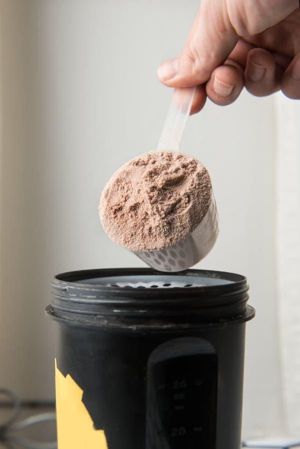 Équipez la main avec le pot et la bouteille préparant la secousse de protéine photos stock