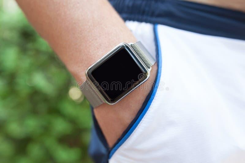Équipez la main avec une montre dans ses shorts de poche image libre de droits