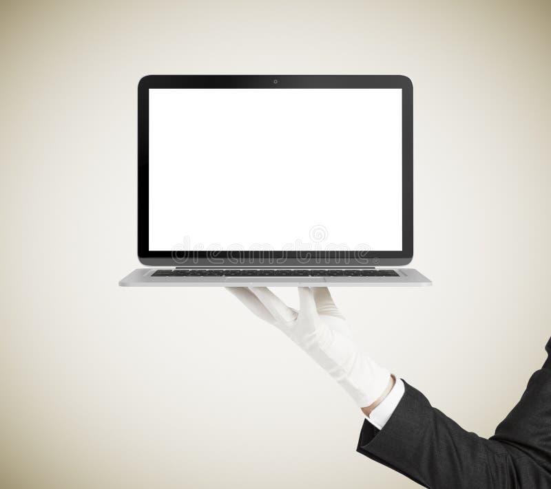 Équipez la main dans le gant blanc tenant l'ordinateur portable avec l'écran vide image libre de droits