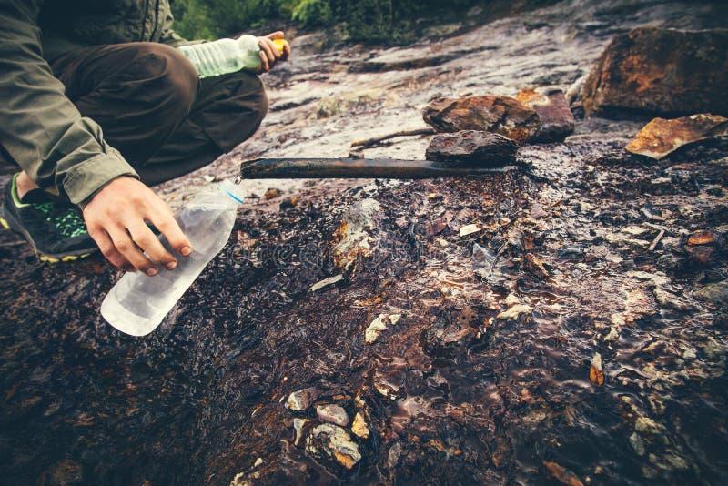Équipez la main de voyageur prenant l'eau dans la bouteille du minerai bien photographie stock libre de droits
