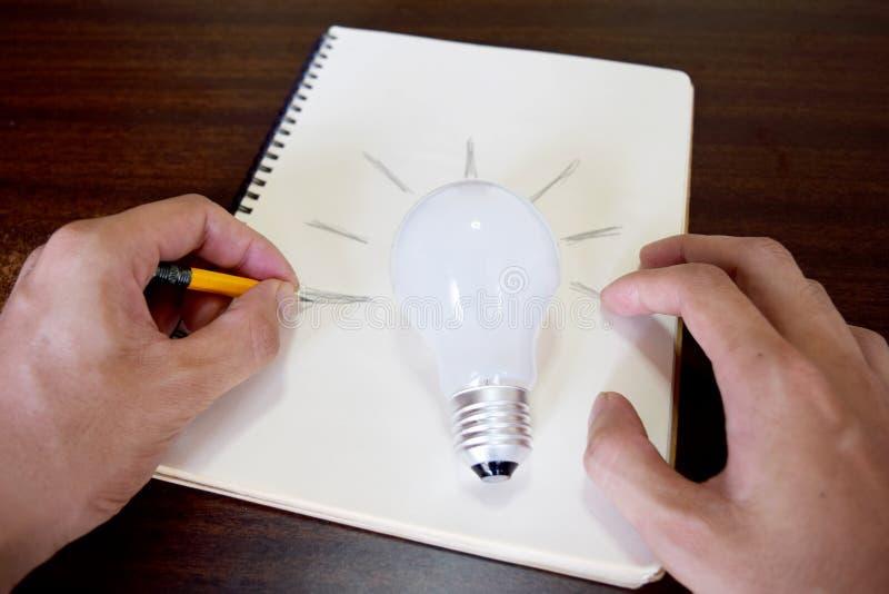 Équipez la main dessinant une ampoule sur le papier de note (le concept d'idée) photos stock