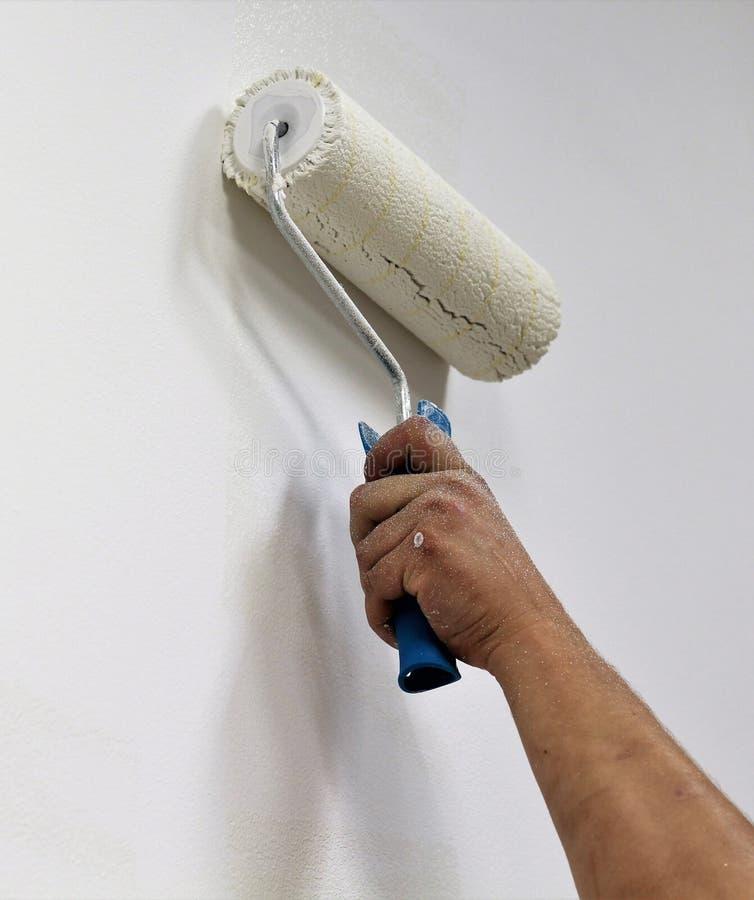 Équipez la main du ` s avec un rouleau de pinceau peignant le mur intérieur dans le blanc photographie stock