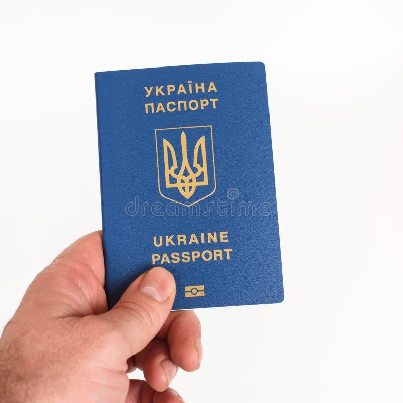 Équipez la main du ` s jugeant le passeport biométrique ukrainien d'isolement sur le fond blanc photographie stock libre de droits
