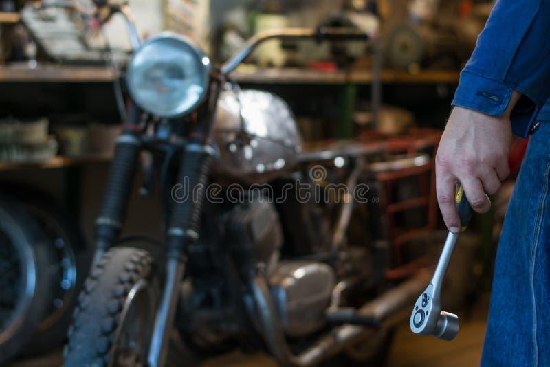 Équipez la main du ` s tenant une clé en métal de prise avec le rochet dans l'orphie photo stock