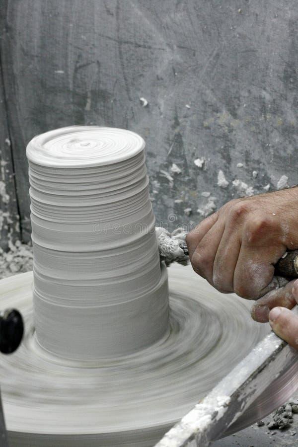 Équipez la main du ` s travaillant à la roue du ` s de potier avec un burin Homme créant la céramique sur la roue de poterie Arti photographie stock libre de droits