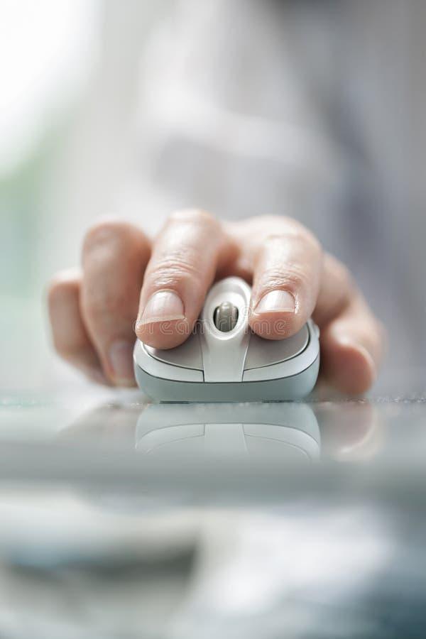 Équipez la main du ` s utilisant la souris sans fil sur la table en verre images stock