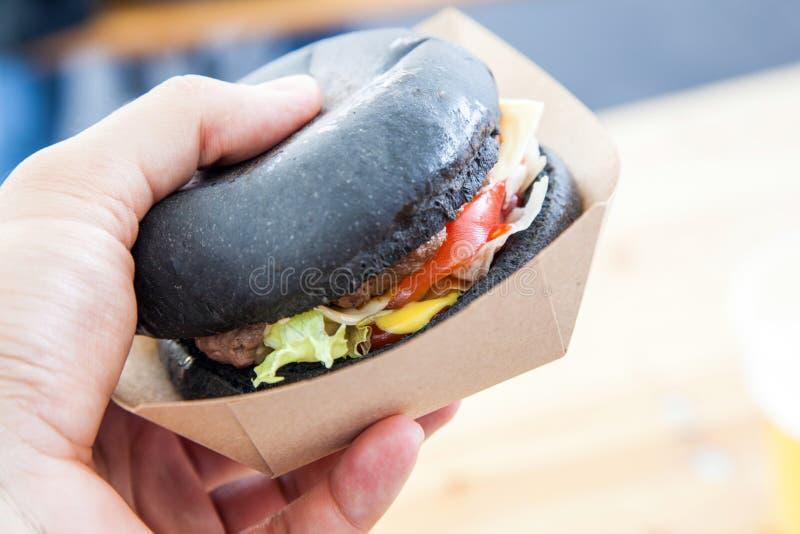 Équipez la main jugeant l'hamburger noir servi sur la boîte de papier au-dessus du su en bois image stock