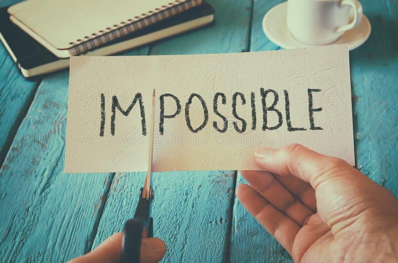 Équipez la main jugeant la carte avec le texte impossible, en coupant le mot im ainsi il possible écrit concept de succès et de d image libre de droits