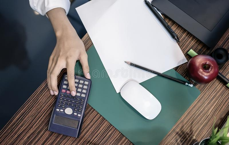 Équipez la main sur la calculatrice et masquez le livre blanc image libre de droits