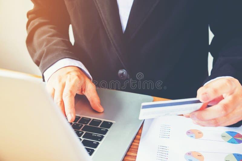 Équipez la main tenant la carte de crédit utilisant la banque en ligne d'ordinateur portable de clavier images stock