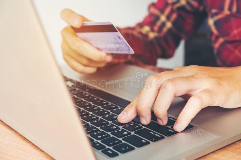 Équipez la main tenant la carte de crédit utilisant la banque en ligne d'ordinateur portable de clavier images libres de droits