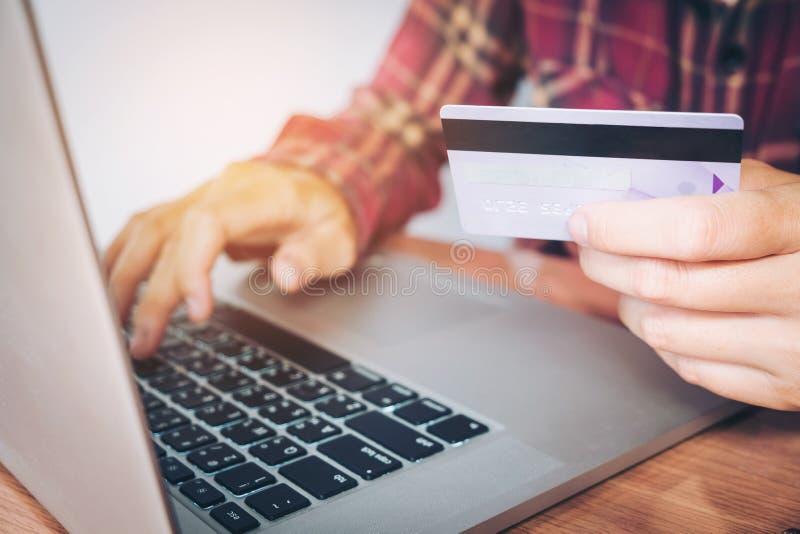 Équipez la main tenant la carte de crédit utilisant la banque en ligne d'ordinateur portable de clavier photo stock