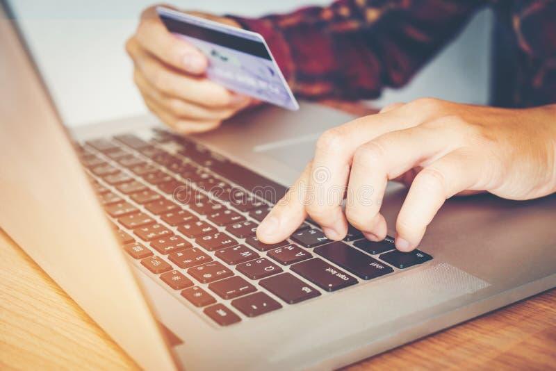 Équipez la main tenant la carte de crédit utilisant la banque en ligne d'ordinateur portable de clavier photos stock
