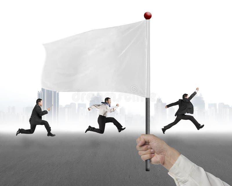 Équipez la main tenant le drapeau avec les hommes d'affaires courant et le Ba de cityscrape photographie stock