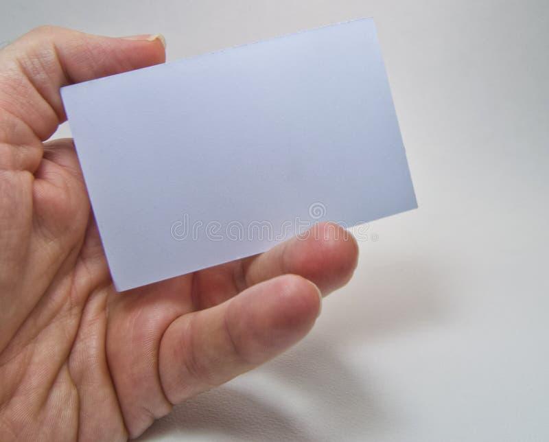 Équipez la main tenant un panneau d'affichage vide gris sur un fond blanc images stock