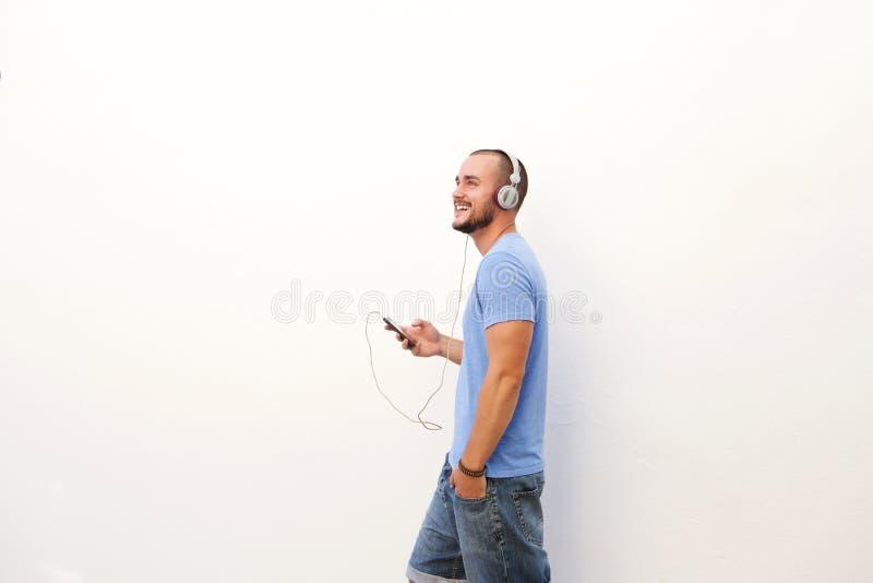 Équipez la marche avec le téléphone portable écoutant la musique sur des écouteurs images libres de droits
