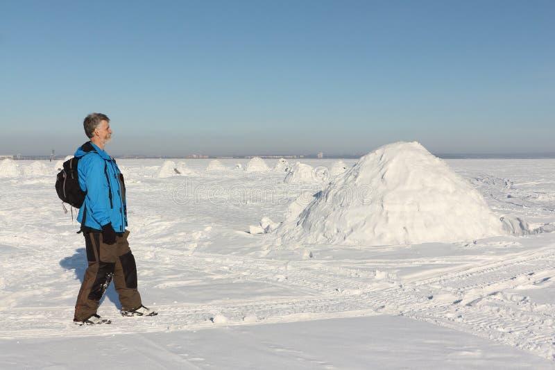 Équipez la marche près d'un igloo sur un réservoir neigeux en hiver images libres de droits