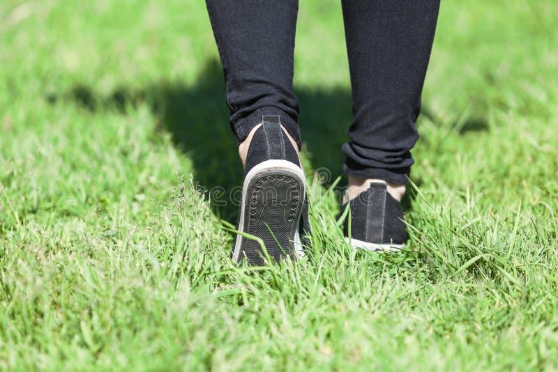 Équipez la marche sur l'herbe dans des chaussures de sports, fermez-vous vers le haut de la vue arrière photos libres de droits