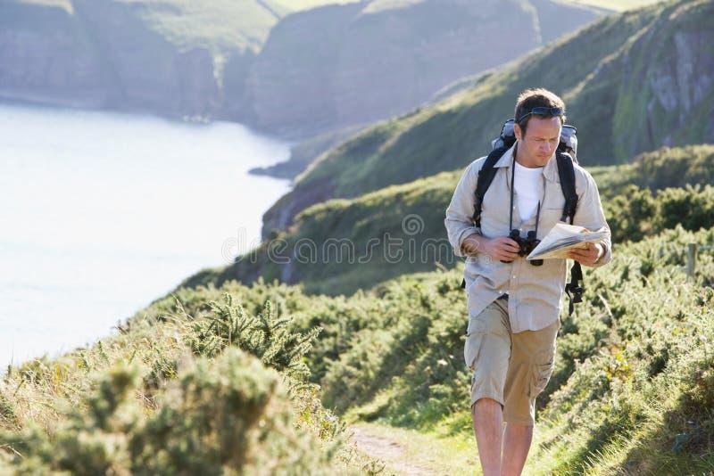 Équipez la marche sur le chemin de côté de falaise regardant la carte images stock