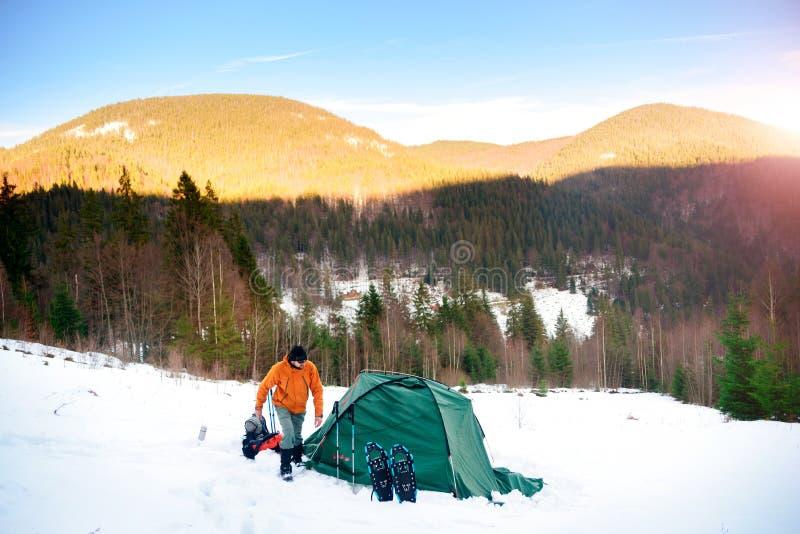 Équipez la marche sur la neige près de la tente en montagnes d'hiver photo stock