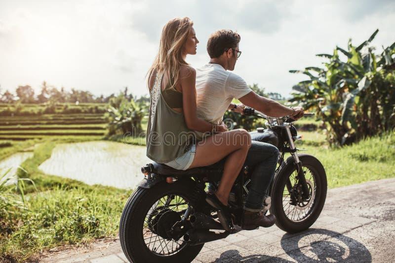 Équipez la moto d'équitation avec une femme sur la route rurale image stock