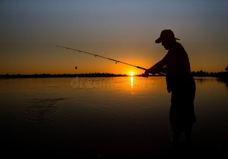 Équipez la pêche sur un lac du bateau au coucher du soleil photos libres de droits