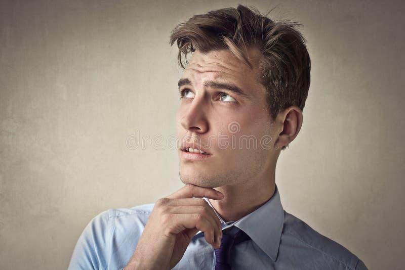 Équipez la pensée avec sa main sur son menton photographie stock