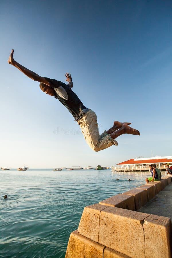 Équipez la plongée outre du mur de bord de mer dans la mer photo stock