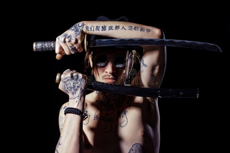 Équipez la pose avec l'épée avec les mains, le cou et le coffre tatoués images libres de droits