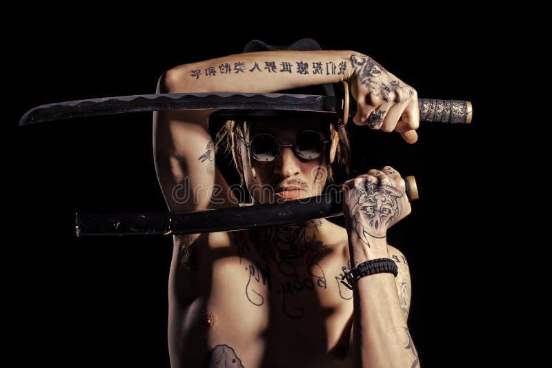 Équipez la pose avec l'épée avec les mains, le cou et le coffre tatoués images stock