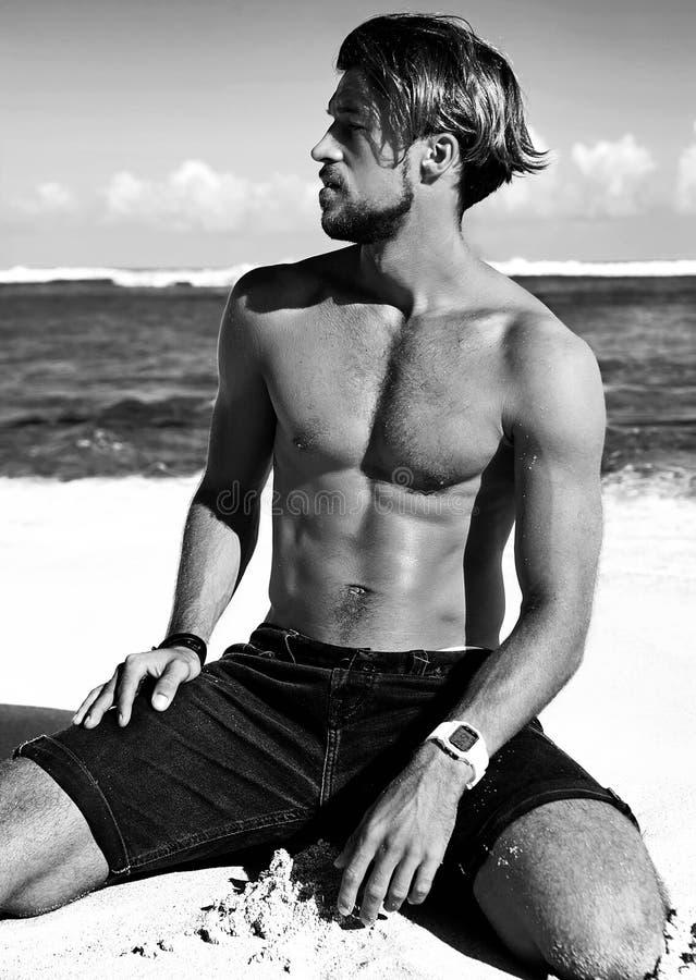 Équipez la pose modèle sur la plage d'été avec le sable blanc sur le fond de ciel bleu et d'océan photos stock