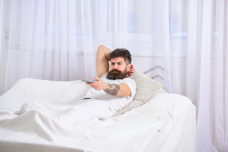 Équipez la pose sur le lit, TV de observation, rideaux blancs sur le fond Type sur le visage sérieux utilisant à télécommande pou photographie stock libre de droits