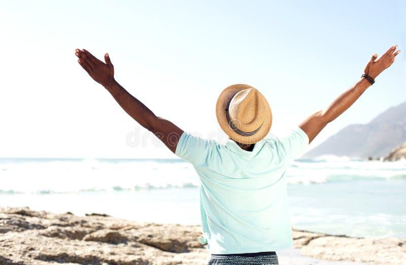 Équipez la position à la plage avec ses mains grandes ouvertes images libres de droits