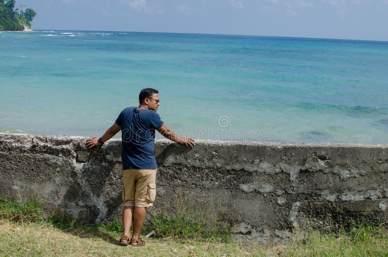 Équipez la position à la plage et regarder la mer image libre de droits