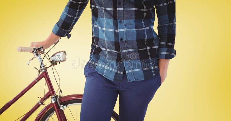 Équipez la position avec sa bicyclette sur le fond jaune image libre de droits